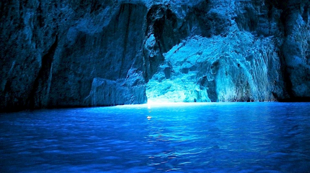 The sunlight enters the Blue Cave opening and illuminates it with the famous blue color